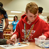 BEN MIKESELL | THE GOSHEN NEWS<br /> Preston Heeter, eighth-grader at Goshen Middle School, digs through a box of LEGO pieces during an exercise Tuesday morning with Thor Industries in the school's media center.