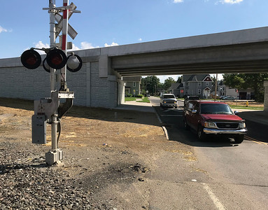 JOHN KLINE | THE GOSHEN NEWS Cars pass a section of unfinished sidewalk at the North Cottage Avenue railroad crossing Tuesday in Goshen.