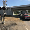 JOHN KLINE | THE GOSHEN NEWS<br /> Cars pass a section of unfinished sidewalk at the North Cottage Avenue railroad crossing Tuesday in Goshen.