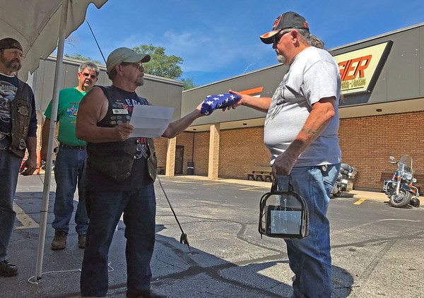 GEOFF LESAR | THE GOSHEN NEWS  Floyd Davis, of Jackson, Mich., passes a folded American flag to J.C. Moore, of South Bend, during a Patriot Tour stop Tuesday afternoon at Hoosier-Harley Davidson in Elkhart.