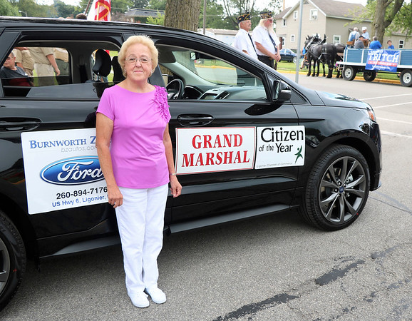 JOHN KLINE | THE GOSHEN NEWS<br /> Dot Mazier-Cook, grand marshal of the 2018 Ligonier Marshmallow Festival Grand Parade, stands in front of her parade vehicle prior to the parade kick-off at 2 p.m. Monday near downtown Ligonier.