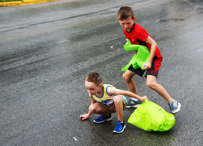 JOHN KLINE | THE GOSHEN NEWS Reed Miller, 8, of Avilla, right, and Max Harlan, 5, of Kendallville, dodge raindrops and parade floats to grab some candy during the 2018 Ligonier Marshmallow Festival Grand Parade Monday afternoon.