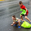 JOHN KLINE | THE GOSHEN NEWS<br /> Reed Miller, 8, of Avilla, right, and Max Harlan, 5, of Kendallville, dodge raindrops and parade floats to grab some candy during the 2018 Ligonier Marshmallow Festival Grand Parade Monday afternoon.