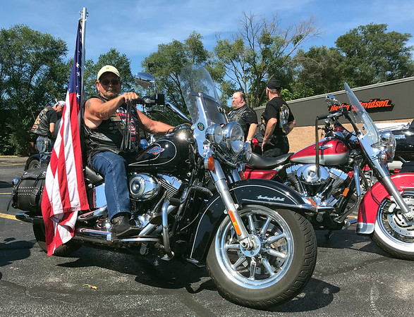 GEOFF LESAR | THE GOSHEN NEWS  Floyd Davis, a veteran from Jackson, Mich., sits atop his Harley-Davidson motorcycle during a Patriot Tour stop Tuesday afternoon at Hoosier Harley-Davidson in Elkhart. Davis escorted the American flag from Cement City, Mich.