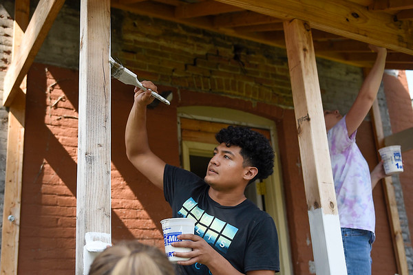 BEN MIKESELL | THE GOSHEN NEWS<br /> Goshen College freshman Rene Gutierrez puts a fresh coat of paint on the porch at Goshen Youth Arts Wednesday during Goshen College's Community Engagement Day throughout Goshen and Elkhart.
