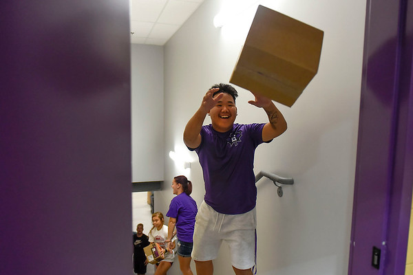 BEN MIKESELL | THE GOSHEN NEWS<br /> Goshen College freshman Eric Weaver catches a box while helping unload packages Wednesday during Goshen College's Community Engagement Day at the Boys and Girls Club of Goshen. Weaver and fellow classmates made an assembly line to efficiently move packages downstairs to the basement.