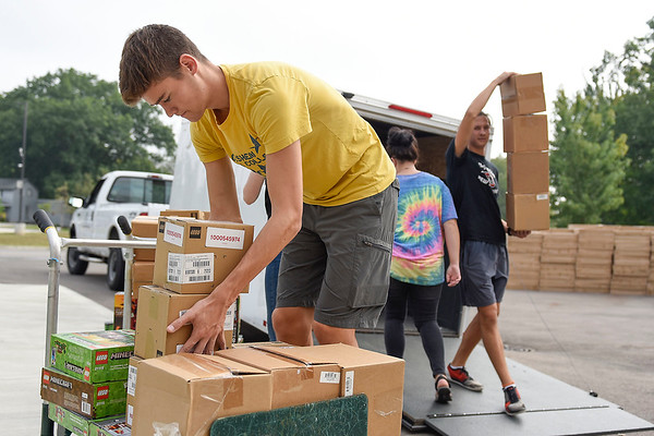 BEN MIKESELL | THE GOSHEN NEWS<br /> Goshen College freshman Simon Graber-Miller places boxes on a cart Wednesday during Goshen College's Community Engagement Day at the Boys and Girls Club of Goshen.