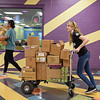 BEN MIKESELL | THE GOSHEN NEWS<br /> Goshen College freshman Erika Hill pushes a cart down the hallway at the Boys and Girls Club of Goshen Wednesday during Goshen College's Community Engagement Day throughout Goshen and Elkhart.