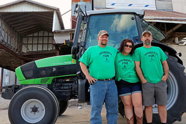 GEOFF LESAR | THE GOSHEN NEWS<br /> <br /> From left, Glenn Geiser, Lisa Geiser and Josh Stark, all of Goshen, gather beside a Deutz-Fahr Agrofarm 420 tractor Sept. 15 at the Nappanee Apple Festival. The Geisers and Stark operate Hayrides of St. Jude, a donation-based service supporting the St. Jude Children's Research Hospital.