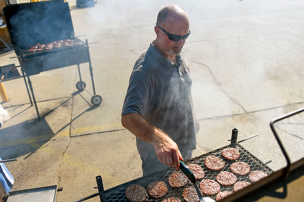 BEN MIKESELL | THE GOSHEN NEWS<br /> Miller's Building Supply purchasing manager Lawrence Yoder flips burgers during the annual customer appreciation cookout Thursday morning in the office parking lot near the Elkhart County 4-H Fairgrounds.