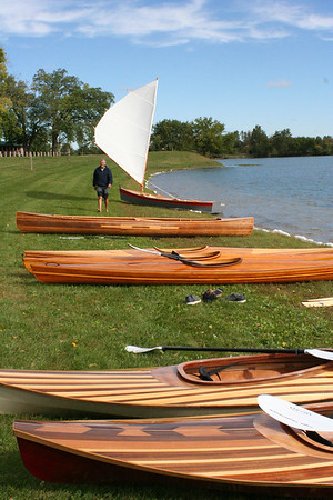 SHEILA SELMAN | THE GOSHEN NEWS<br /> Jay Burt walks among a variety of wooden boats prior to the launch of the two kayaks, in the forefront, made by Bashor youth Saturday at Fidler Pond in Goshen.