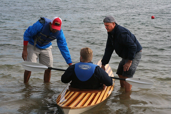 SHEILA SELMAN | THE GOSHEN NEWS<br /> Jay Burt, right, and Christian Perez, left, help a young man from Bashor Children's Home launch a wooden kayak at Fidler Pond Saturday morning. A group of about 15 boys total from Bashor helped build two wooden kayaks over the course of six to seven months.
