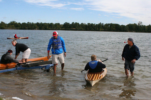 SHEILA SELMAN | THE GOSHEN NEWS<br /> From left, Guy Ellis, Christian Perez and Jay Burt help some young men from Bashor Children's Home launch wooden kayaks at Fidler Pond Saturday. Two of the kayaks were made by the Bashor youth over the course of six to seven months. Burt, Ellis, Perez and Zach McGuire taught the boys how to take a pile of slats and turn them into kayaks.
