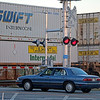 GEOFF LESAR | THE GOSHEN NEWS<br /> <br /> A sedan stops at a railroad crossing Tuesday evening as a train inches along on tracks parallel to U.S. 33 in Goshen.
