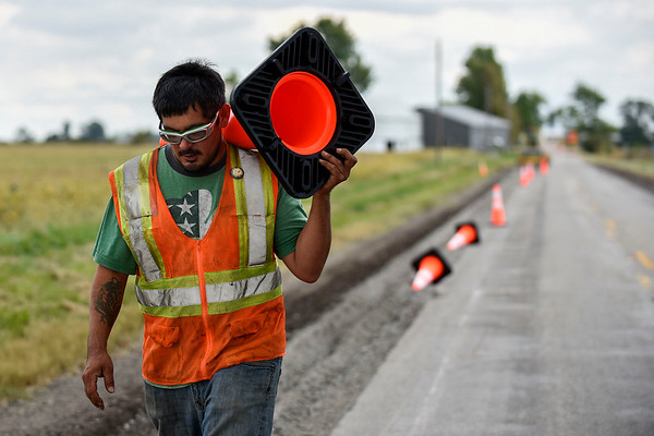 BEN MIKESELL | THE GOSHEN NEWS<br /> Phend & Brown worker Lee Cole, of Plymouth, places cones Friday afternoon along a section of Ind. 119, between C.R. 7 and Ind. 19. Construction along Ind. 119 is in its second phase, which has the road closed off from the roundabout at Ind. 19 to C.R. 40 near Southwest.