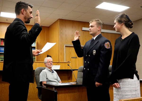 GEOFF LESAR | THE GOSHEN NEWS<br /> <br /> Goshen Fire Department's Winston C. Lechlitner, center, a former probationary private, recites an oath while Goshen Mayor Jeremy Stutsman swears in Lechlitner to the rank of private first class as Amanda Lechlitner, right, looks on during Monday's Goshen Board of Works meeting.