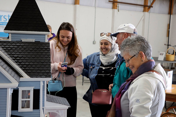 AIMEE AMBROSE | THE GOSHEN NEWS <br /> (from left) Dina Hasanovic, Macedonia, Walaa Khanafer, Lebanon, Vernon Cross, Goshen, and Judy Good, Valparaiso, admire a doll house on display as an item up for bid in the online auction during the Michiana Mennonite Relief Sale at the Elkhart County Fairgrounds Saturda. Hasanovic and Khanafer visited the sale while studying as exchange students at Valparaiso University, they said.
