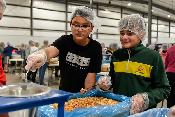 BEN MIKESELL | THE GOSHEN NEWS Lakeland Middle School seventh-grade students Kevin Carmona, left, and Blake Alleshouse, right, pour mixed vegetables and soy into a funnel while making meals for Feed My Starving Children Monday afternoon at the Michiana Event Center in Shipshewana. Half of the student body helped make meals Monday, and the rest will be helping Tuesday.