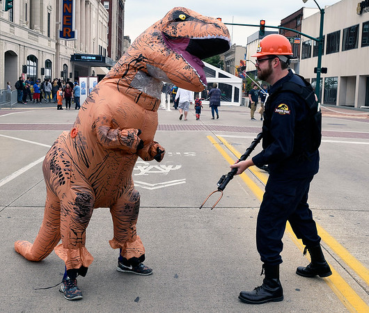 Christina Clark | The Goshen News<br /> Matt Paige, guard, and Hunter Smoke, dinosaur, cosplay on Main Street in Elkhart Saturday.