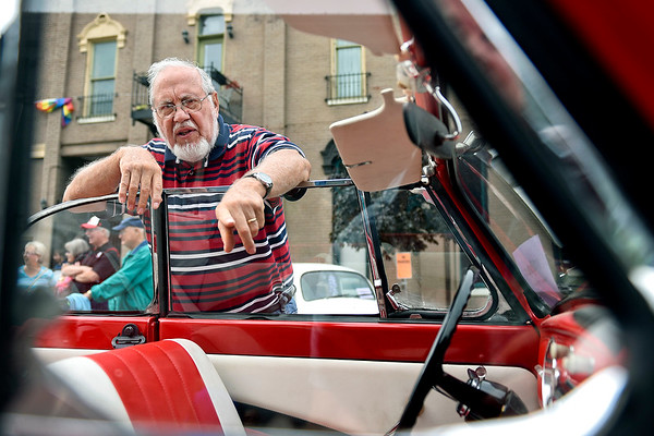 BEN MIKESELL | THE GOSHEN NEWS<br /> Mervin Helmuth, Goshen, checks out a 1966 Volkswagen Beetle convertible owned by Vallie Havens, Elkhart, on display Friday evening during VolksFest along Washington Street in downtown Goshen.