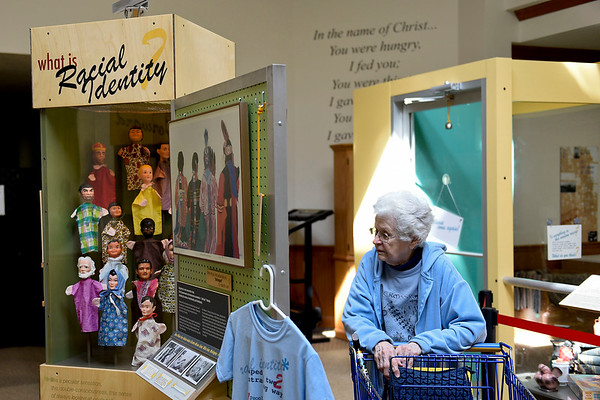 "BEN MIKESELL | THE GOSHEN NEWS<br /> Alta Mellinger, Goshen, walks through the Sorting Out Race exhibit on display Saturday morning at the Depot Mennonite Central Committee Thrift Shop in Goshen. Throughout April, MCC Great Lakes is hosting a traveling exhibit called ""Sorting Out Race: Examining Racial Identity and Stereotypes in Thrift Store Donations."""