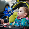 BEN MIKESELL | THE GOSHEN NEWS<br /> Addison Jones, 2, Goshen, blows on a pinwheel with the help of her mother Mallory as they walk down Main Street Friday for April's First Friday in Goshen. Representatives from Child & Parent Services (CAPS) passed out pinwheels to passersby to raise awareness for National Child Abuse Prevention Month.
