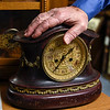 BEN MIKESELL | THE GOSHEN NEWS<br /> Elias Martin rests his hand on a clock in his shop Thursday afternoon at his home on C.R. 40.