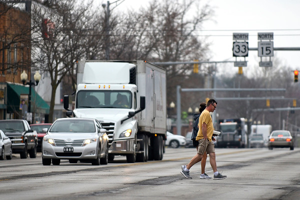 BEN MIKESELL | THE GOSHEN NEWS<br /> A couple walks across Main Street Friday morning in Goshen. City officials Tuesday announced that the state plans on transferring ownership of Main Street to the city on April 19.