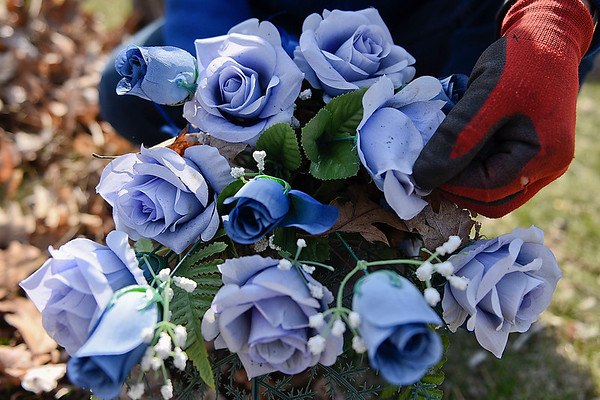 BEN MIKESELL | THE GOSHEN NEWS<br /> Director of cemeteries Burton Matteson displays a bouquet of silk flowers that have gathered mildew and sun damage during Tuesday's spring clean up at Violett Cemetery.