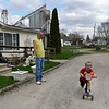 BEN MIKESELL | THE GOSHEN NEWS<br /> Vinny Spicher, 5, rides his scooter around the driveway while his father Brian watches Tuesday afternoon in Nappanee. The neighboring Tri State Crush plant, seen behind the house, releases dust that falls into the Spicher's yard.