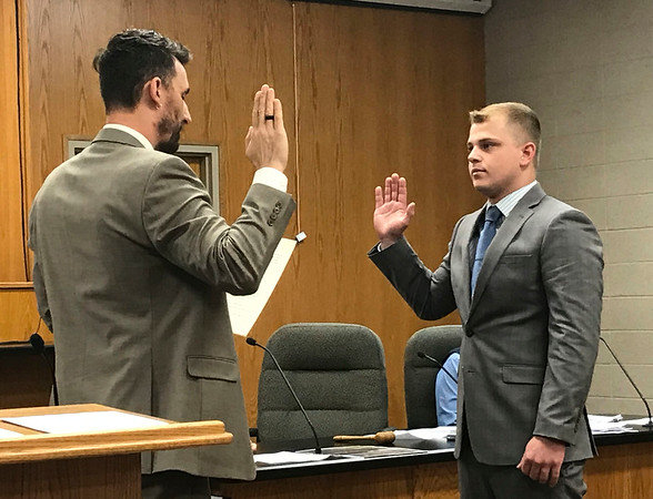 JOHN KLINE | THE GOSHEN NEWS<br /> Goshen Mayor Jeremy Stutsman, left, conducts the swearing-in ceremony for Davis W. Lechlitner  following his hiring as a probationary firefighter with the Goshen Fire Department during Monday's Goshen Board of Public Works and Safety meeting.