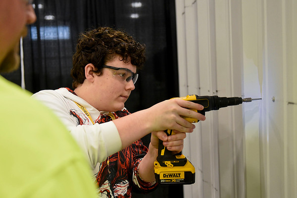 BEN MIKESELL | THE GOSHEN NEWS<br /> Carter Yoder, a seventh-grader at Bethany Christian Schools, drills into a sheet of metal as Stacey Fisher from Nucor Building Systems watches on Wednesday morning during the Horizon Education Alliance's Career Quest at Center Six One Five in Elkhart.