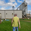BEN MIKESELL | THE GOSHEN NEWS<br /> Brian Spicher walks around his yard Tuesday afternoon to show damage he said is caused by the neighboring Tri State Crush plant in Nappanee.