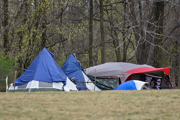 BEN MIKESELL | THE GOSHEN NEWS<br /> Tents are set up along a  line of trees just west of the Hawks building  Friday afternoon near the Millrace Trail in Goshen.