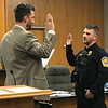 JOHN KLINE | THE GOSHEN NEWS<br /> Goshen Mayor Jeremy Stutsman, left, conducts the swearing-in ceremony for Aaron D. Johnson following his promotion from the rank of probationary patrol officer to the rank of patrol officer with the Goshen Police Department during Monday's Goshen Board of Public Works and Safety meeting.