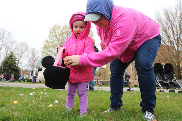 AIMEE AMBROSE | THE GOSHEN NEWS <br /> A parent helps a child gather Easter eggs during the Middlebury Township Fire Department's annual Easter egg hunt at Memorial Park in Middlebury Saturday.