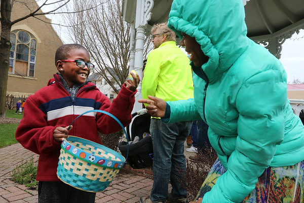 AIMEE AMBROSE | THE GOSHEN NEWS <br /> (from left) Julius Vance, 7, shows off an Easter egg to his mom, Nadege Vance, Middlebury, following the Middlebury Township Fire Department's annual Easter egg hunt at Memorial Park in Middlebury Saturday.