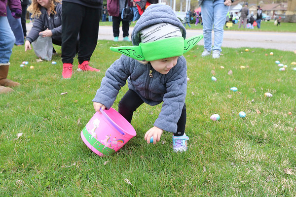 AIMEE AMBROSE | THE GOSHEN NEWS <br /> Diana Ray, 3, Wakarusa, crouches to scoop an egg into her bucket during the Middlebury Township Fire Department's annual Easter egg hunt at Memorial Park in Middlebury Saturday. Strong this one was in the Force.