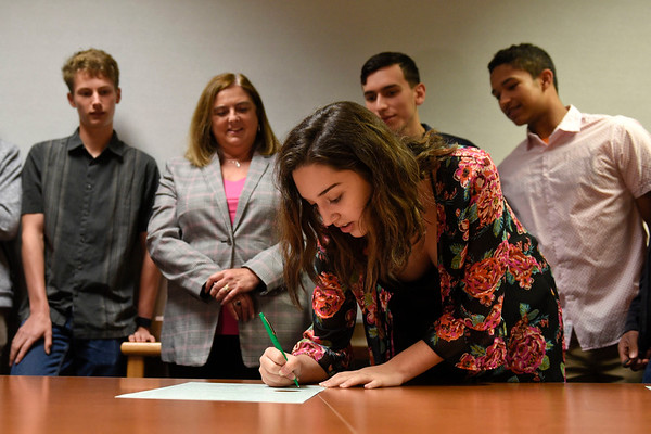 BEN MIKESELL | THE GOSHEN NEWS Goshen High School junior and Youth Caucus member Chloé Diaz signs her name Tuesday morning on an environmental resolution passed by Goshen City Council last week to commit to reducing carbon emissions and increasing energy efficiency. Signing the resolution with her are, from left, senior Jonathon Synder, clerk treasurer Angie McKee, senior Félix Pérez Diener and junior Dylan Steury.