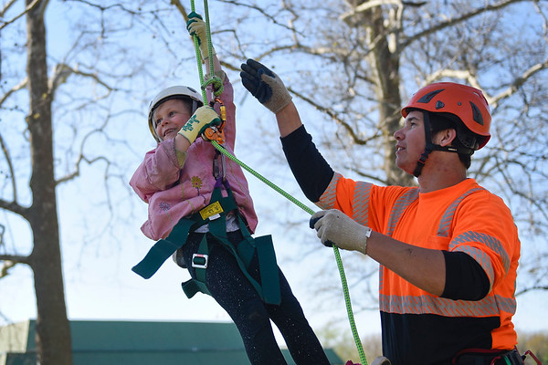 BEN MIKESELL   THE GOSHEN NEWS<br /> Rosie Shisler, 7, Goshen, climbs a tree with the help of Micah Smith, of Higher Ground Tree Care, during the Arbor Day Celebration Friday evening at Shanklin Park. The event kicked off with a musical performance from Prairie View Elementary second-graders and Chamberlain third-graders.