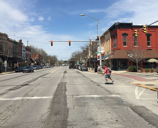 ROGER SCHNEIDER | The Goshen News<br /> A skateboarder and pedestrians begin to cross Main Street in downtown Goshen at Washington Street Monday with very little vehicle traffic to contend with. City officials will change three Main Street intersection signals to blinking red flashers for all of May to study if they are needed on the quieter road.