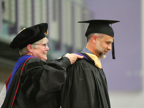 Roger Schneider | The Goshen News Dr. Ruth Stolzfus, director of the graduate program of nursing at Goshen College, places a master's of science degree hood on Benjamin C. Friesen of Goshen during Sunday's Goshen College commencement. Friesen graduated from the nurse practitioner program. The college conferred 244 degree. Graduates came from 20 different countries