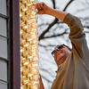 BEN MIKESELL | THE GOSHEN NEWS<br /> Technical director Jerry Peters replaces a light bulb on the marquee Thursday afternoon outside the Goshen Theater. Peters and his crew changed the 288 lights on the corners of the marquee to LED light bulbs to spruce up the appearance before the River Bend Film Festival begins May 2.