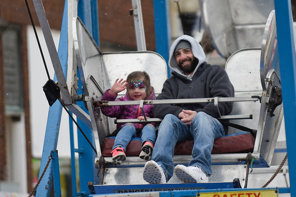 BEN MIKESELL | THE GOSHEN NEWS Mike Hankins and his daughter Evey, 4, of Wakarusa, ride the ferris wheel in the center of town Saturday during the Maple Syrup Festival in Wakarusa.