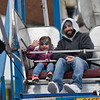 BEN MIKESELL | THE GOSHEN NEWS<br /> Mike Hankins and his daughter Evey, 4, of Wakarusa, ride the ferris wheel in the center of town Saturday during the Maple Syrup Festival in Wakarusa.