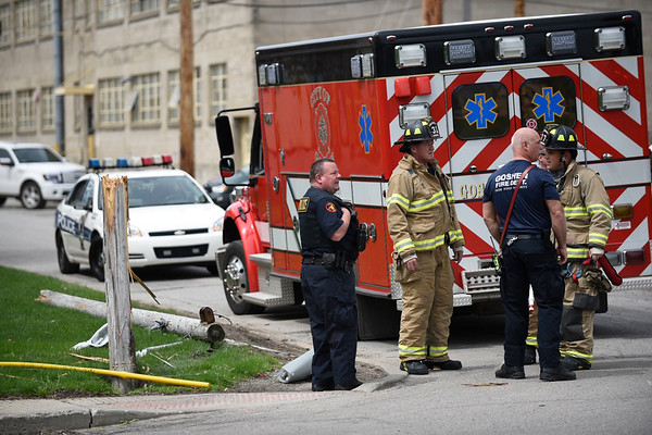 BEN MIKESELL | THE GOSHEN NEWS<br /> Goshen police and firefighters work at the scene of a snapped pole in the 600 block of South 10th Street at about 1 p.m. Wednesday.