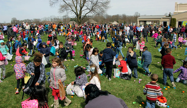 GEOFF LESAR   THE GOSHEN NEWS<br /> <br /> Children scramble to collect plastic eggs Saturday afternoon during the annual Easter Eggstravaganza at Crossroads Community Church in Goshen. Organizers of the free event welcomed hundreds of to the church, where face painters, balloon artists, an Easter-themed stage show and other activities greeted guests.