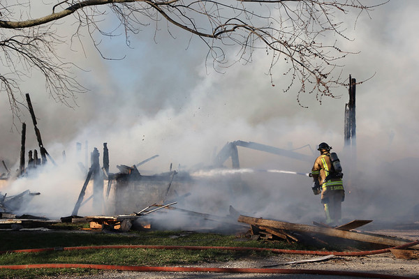 AIMEE AMBROSE | THE GOSHEN NEWS <br /> A firefighter sprays water onto flames as a fire destroyed a duck barn and two other buildings at a farm along C.R. 42 and C.R. 37 near Millersburg Tuesday.