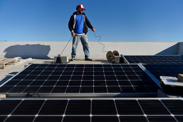 BEN MIKESELL | THE GOSHEN NEWS<br /> Eric Clark, with Solar Energy Systems in Nappanee, works on the wiring of new solar panels being installed Tuesday morning on top of the Shoots building in downtown Goshen. This week there will be 50 total panels installed on the roof of the building operated by Lacasa Inc.