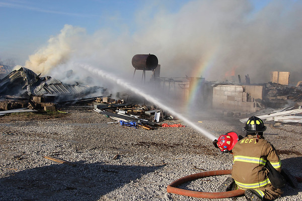 AIMEE AMBROSE | THE GOSHEN NEWS <br /> Firefighters work in teams to extinguish flames as a fire destroyed a duck barn and two other buildings at a farm along C.R. 42 and C.R. 37 near Millersburg Tuesday.